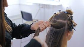 Peluquero profesional que hace el peinado para la mujer bonita joven almacen de video