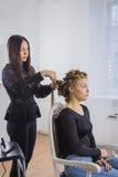 Peluquero profesional que hace el peinado para la mujer bonita joven con el pelo largo Foto de archivo libre de regalías