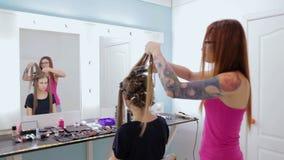 Peluquero profesional que hace el peinado para la mujer bonita joven con el pelo largo almacen de metraje de vídeo