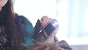 Peluquero profesional que hace el peinado para la mujer bonita joven - la fabricación se encrespa Fotografía de archivo libre de regalías