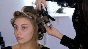 Peluquero profesional que hace el peinado para la mujer bonita joven - la fabricación se encrespa Foto de archivo