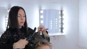 Peluquero profesional que hace el peinado para la mujer bonita joven - la fabricación se encrespa almacen de video