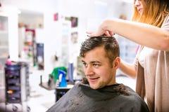 Peluquero profesional que hace nuevo corte de pelo a su clie hermoso imagen de archivo