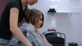 Peluquero profesional que prepara al cliente de la mujer para el pelo de teñido almacen de metraje de vídeo