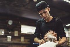 Peluquero que afeita al cliente Fotos de archivo