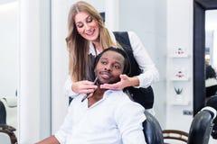 Peluquero que afeita al cliente en su salón Imagen de archivo libre de regalías