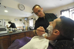 Peluquero que afeita con el cepillo que afeita espuma al hombre joven Imagen de archivo