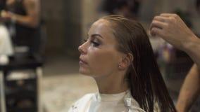 Peluquero que cepilla el pelo mojado de la mujer hermosa antes de peinado en estudio de la belleza Peluquero que peina el pelo fe almacen de video