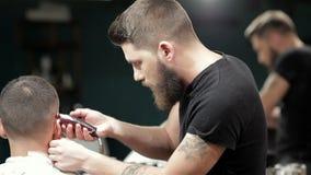Peluquero que corta al hombre brutal barbudo, reflexión adentro almacen de metraje de vídeo