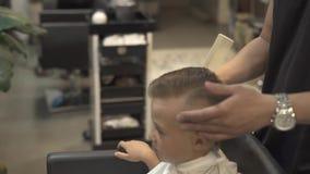Peluquero que corta al niño pequeño del pelo con las tijeras y el peine en salón de la peluquería Concepto del corte de pelo del  metrajes