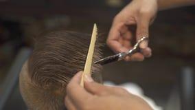 Peluquero que corta el pelo con las tijeras del peluquero en salón de la peluquería de los niños Corte de pelo de los niños con l almacen de video