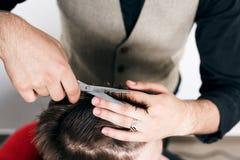 Peluquero que da un nuevo corte de pelo al cliente barbudo joven Imagen de archivo libre de regalías