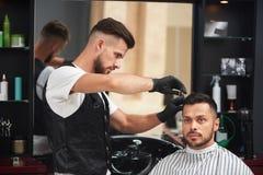 Peluquero que diseña el corte de pelo del hombre que usa el peine y las tijeras foto de archivo