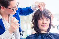 Peluquero que diseña el pelo de la mujer en tienda imagenes de archivo