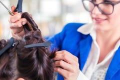 Peluquero que diseña el pelo de la mujer en tienda imagen de archivo
