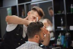 Peluquero que diseña el pelo y la barba del ` s del cliente en barbería imagen de archivo libre de regalías