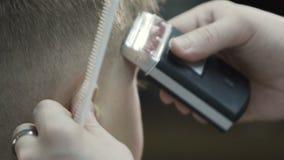 Peluquero que hace corte de pelo con el condensador de ajuste Un niño pequeño lindo consigue su corte de pelo en la peluquería de almacen de video