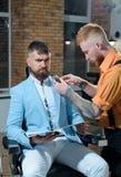 Peluquero que hace corte de pelo de hombre barbudo atractivo en peluquer?a de caballeros Tan de moda y elegante Individuo brutal  imagen de archivo libre de regalías