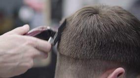 Peluquero que hace corte de pelo usando la máquina almacen de video