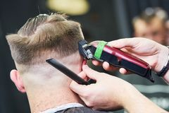 Peluquero que hace el corte de pelo masculino Pelo del corte del peluquero del cliente imagen de archivo libre de regalías