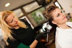 Peluquero que hace el tratamiento del pelo a un cliente en salón Fotografía de archivo