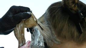 Peluquero que hace la coloración del cabello para la mujer joven Concepto de la belleza, del peinado y de la gente Cámara lenta almacen de video