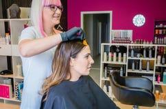 Peluquero que muestra la muestra del tinte de pelo a la mujer joven Foto de archivo libre de regalías