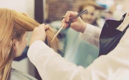 Peluquero que nivela y que corta el pelo a la mujer rubia joven con Fotos de archivo