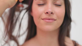 Peluquero que peina el pelo de una mujer sonriente metrajes