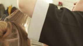 Peluquero que peina el pelo femenino y que corta con las tijeras de la peluquería en salón de belleza Ciérrese encima de la fabri almacen de metraje de vídeo