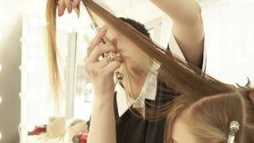 Peluquero que peina el pelo femenino y que corta con las tijeras profesionales en salón de la peluquería Ciérrese encima de la fa almacen de video