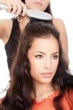 Peluquero que peina el pelo negro largo de la mujer Foto de archivo libre de regalías