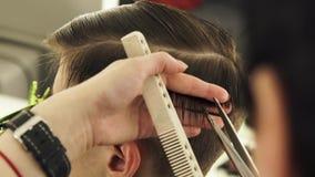 Peluquero que peina el pelo y que corta con las tijeras de la peluquería en cierre de la escuela de la belleza para arriba Peluqu almacen de video