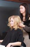 Peluquero que peina a la muchacha rubia del cliente femenino en salón de la peluquería Imágenes de archivo libres de regalías