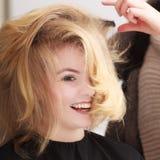 Peluquero que peina a la muchacha rubia del cliente femenino en salón de la peluquería Fotografía de archivo