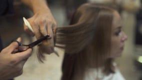 Peluquero que peina y que corta el pelo largo con las tijeras en barbería Corte de pelo y cuidado de la mujer en estudio de la be metrajes