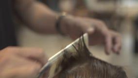 Peluquero que peina y que corta el pelo mojado con las tijeras del peluquero en el cierre masculino del salón para arriba Corte d metrajes