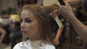Peluquero que peina y que endereza el pelo con hierro del pelo en salón de la peluquería Peluquero que hace el peinado femenino c almacen de video