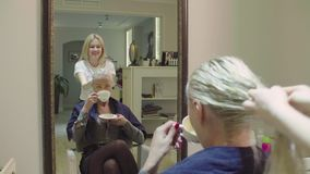 Peluquero que se aplica diseñando el gel al pelo del cliente almacen de metraje de vídeo