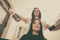 Peluquero que seca el pelo femenino oscuro usando hairdryer profesional fotografía de archivo
