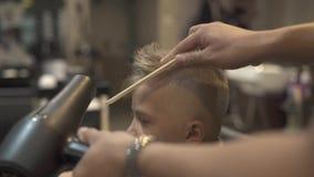 Peluquero que usa el secador y el peine de pelo para el peinado del muchacho en salón Sequedad del pelo de los niños en peluquerí almacen de metraje de vídeo