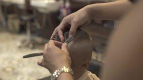 Peluquero que usa la maquinilla de afeitar recta para afeitar el pelo en la cabeza del niño pequeño en salón de la peluquería Cie metrajes