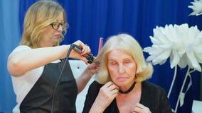 Peluquero que usa las pinzas del pelo que encrespan el pelo de la mujer mayor en estudio de la belleza metrajes