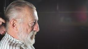Peluquero que visita del hombre mayor en peluquería de caballeros almacen de metraje de vídeo