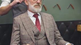 Peluquero que visita del hombre mayor en peluquería de caballeros metrajes