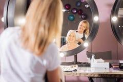Peluquero sonriente que experimenta con corte de pelo de los clientes Imagenes de archivo