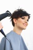 Peluquero Using Dryer en el pelo mojado de la mujer en salón.  Pelo corto. Foto de archivo libre de regalías