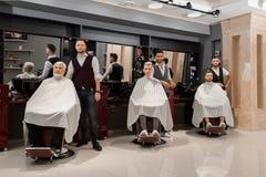 Peluqueros que colocan a los clientes cercanos cubiertos con los cabos y que se sientan en sillas del peluquero imagen de archivo
