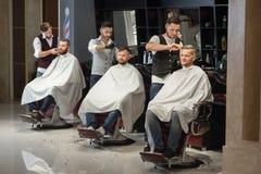 Peluqueros que preparan y que diseñan cortes de pelo de clientes en barbería fotos de archivo