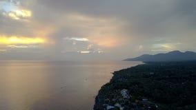 Pemuteran, вид с воздуха от трутня, каменистого берега моря и гор на заходе солнца Индонезия тюкованный видеоматериал